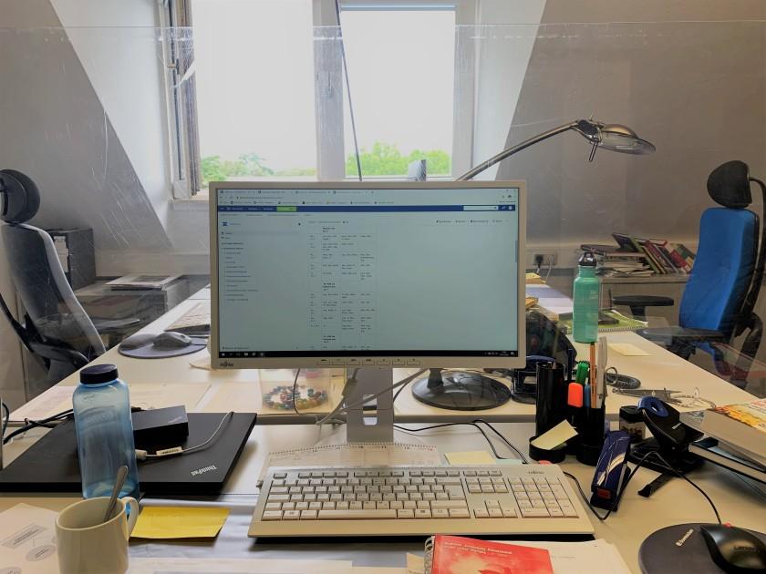 Büro mit Schreibtischen, Bildschirm und Tastatur