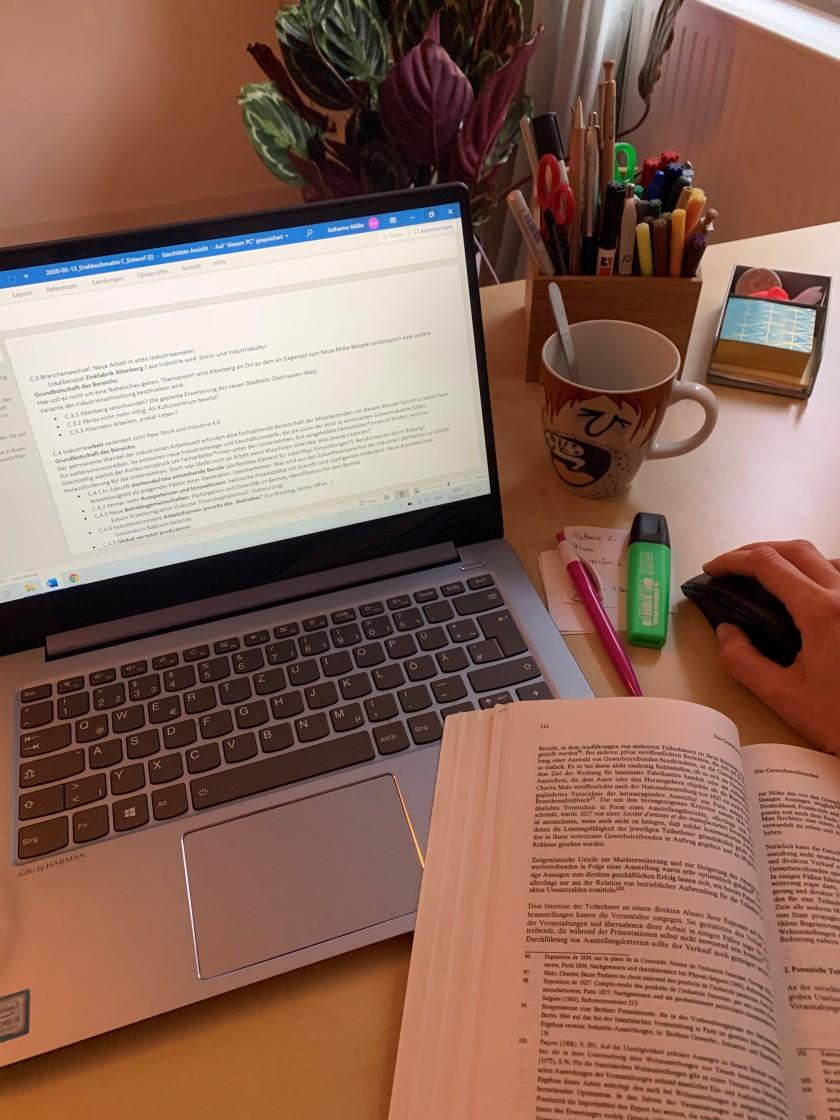 Schreibtisch mit Laptop und aufgeschlagenem Buch