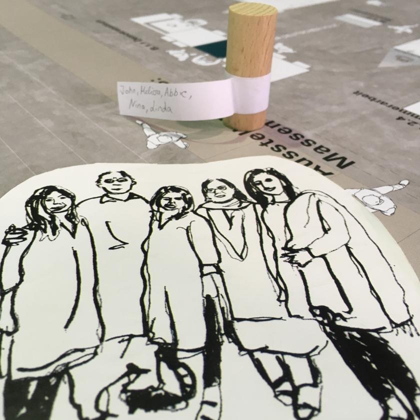 Holzfigürchen und Kärtchen mit Zeichnung von Menschen
