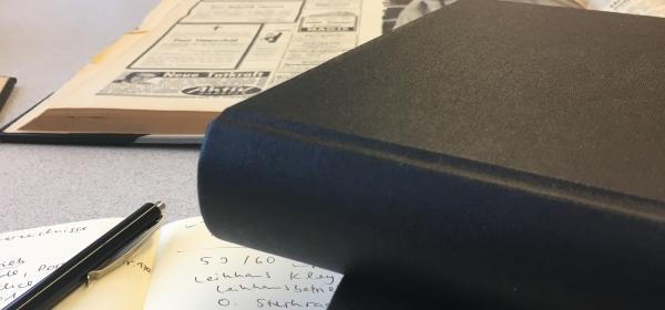 Leseraum im Stadtarchiv Oberhausen. Auf einem Tisch liegen Branchenbücher und ein aufgeschlagenes Notizheft.