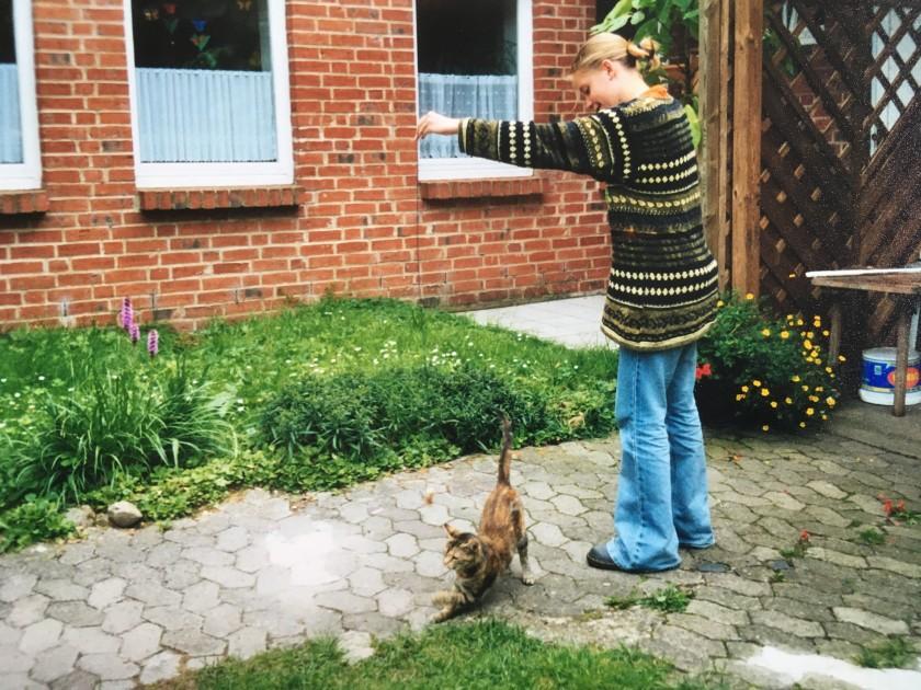 Jugendliche in Schlagjeans, Doc Martens und Riesenpulli spielt mit einer Katze.